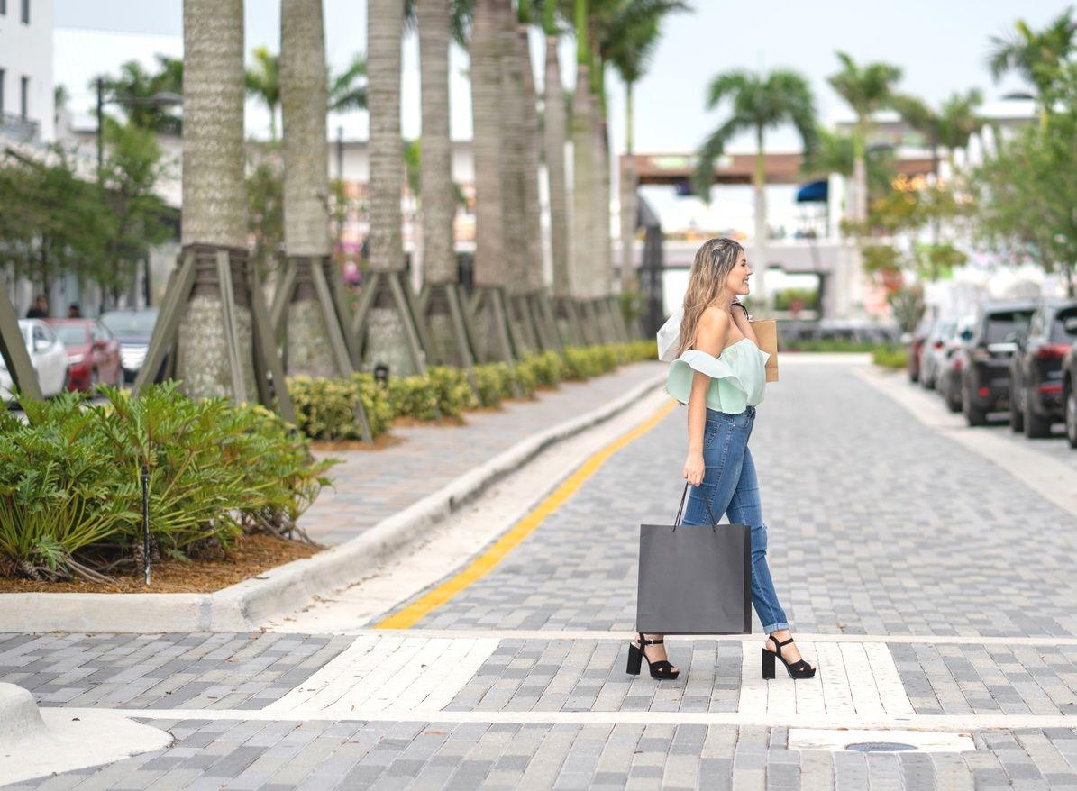 una mujer que sostiene una bolsa de compras y cruza la calle en Coral Gables